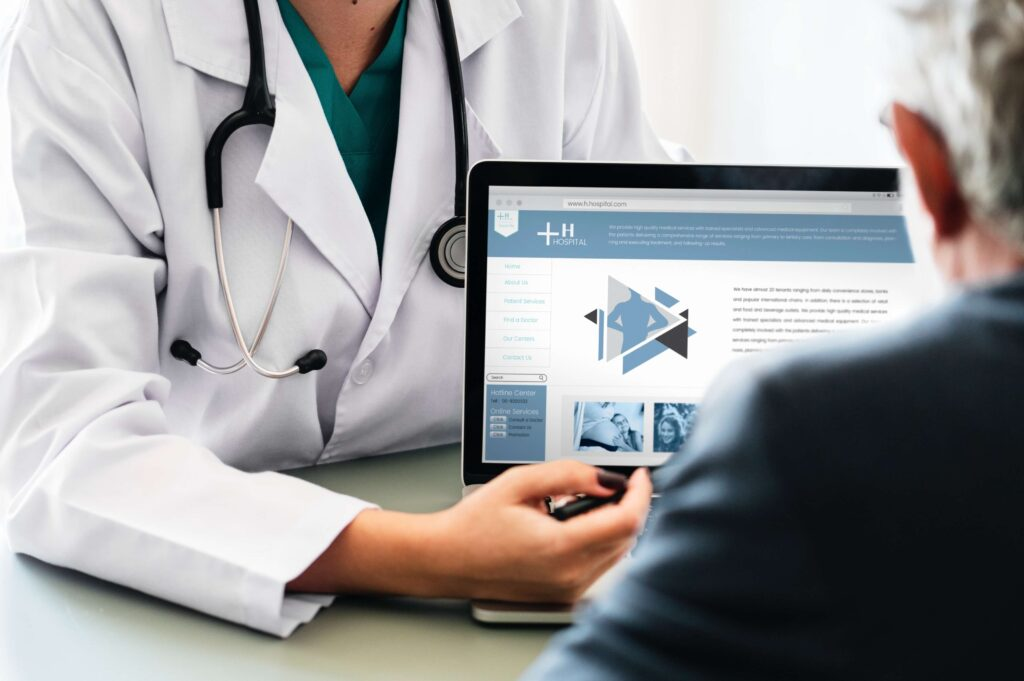 A doctor showing a patient information on a laptop screen.