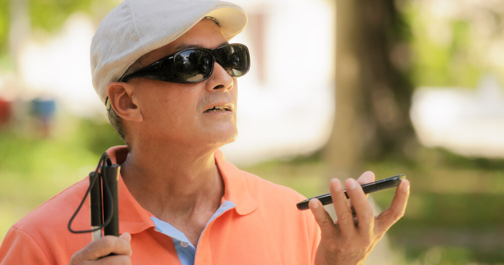 Photo of a blind man talking on his mobile phone