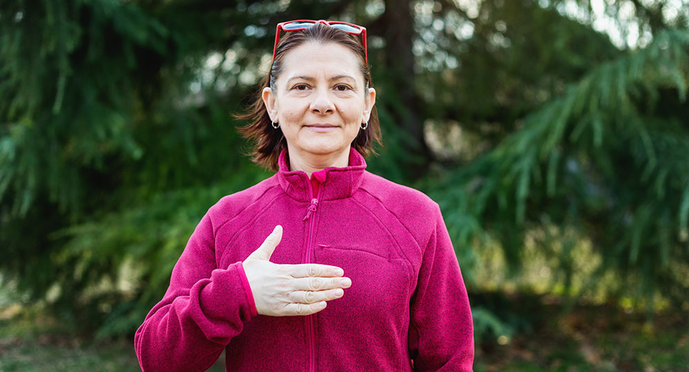 A deaf woman using sign language to sign the word please