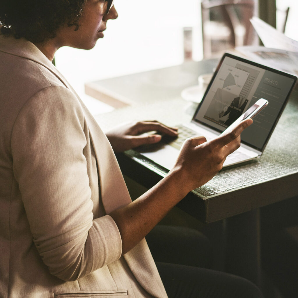 A business woman in a coffee shop looking at her phone while using her laptop