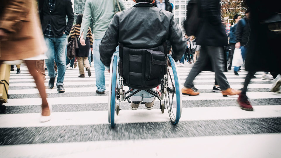 A man in a wheelchair crossing a busy street