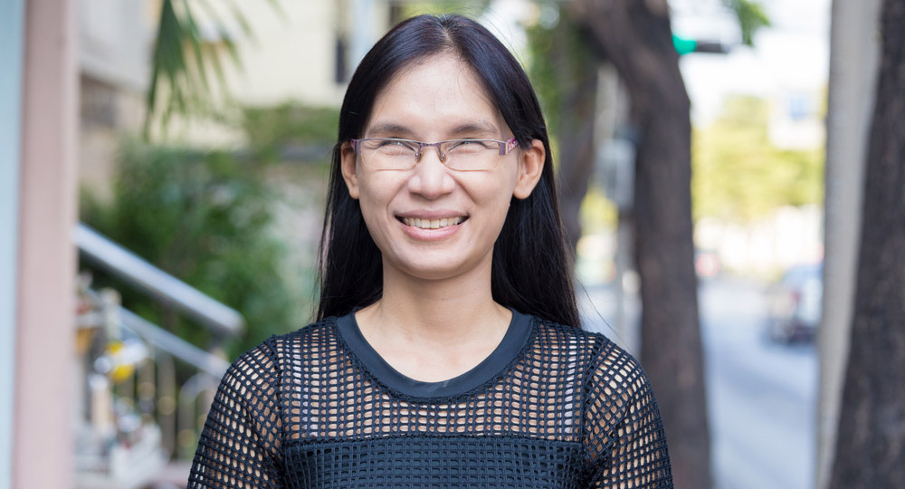 An Asian lady wearing glasses who is blind or vision-impaired standing on the street and smiling