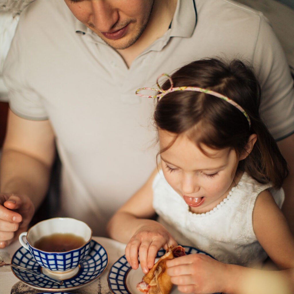 Little girl sitting on her father's knee eating dessert